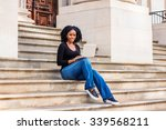 Small photo of African American college student studying in New York. Wearing long sleeves, V neck top, jeans, leather sneakers, a girl sitting on stairs, working on laptop computer. Filtered look with blue tint.