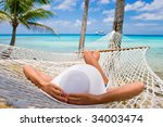 Woman Relaxing On Hammock With...