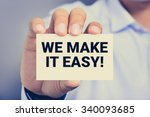 Small photo of WE MAKE IT EASY! message on the card shown by a man, vintage tone
