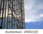 Architectural detail of a contemporary building reflecting a cloudy sky - stock photo