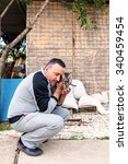 Small photo of Hunedoara, Romania - June 21, 2014: Dark Haired Man With Mustache With Toady Grey Kitten