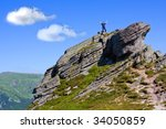 Man stay on rock top in mountains - stock photo