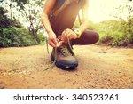 Woman Hiking Tying Shoelace On...