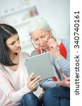 helping old woman use a tablet... | Shutterstock . vector #340740161