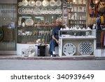 Bored Shopkeeper On Side Of...