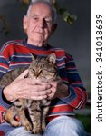 Old Man Holding Tabby Cat In...