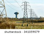 Small photo of Power lines and a water tower in the background. Water and power are essential for every modern society. Power lines stretch over some wetland toward the city. Houses are visible behind some trees.