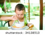 portrait of a cute kid eating... | Shutterstock . vector #34138513