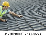 Builder Working On Roof Of New Building - stock photo