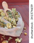 Small photo of Dry cones of american hop (Humulus lupulus) flowers on wooden background