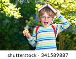 Small photo of Funny adorable little kid boy with glasses, books, apple and backpack on his first day to school or nursery. Child outdoors on warm sunny day, Back to school concept