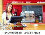 Small photo of young female cashier operating at the cash desk in cafe