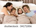 happy family laying in bed | Shutterstock . vector #34171006