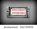 Small photo of Filing cabinet drawer label with the words Success Stories in red text. Processed in black and white for effect