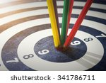 Small photo of color pencils in bull's eye Success hitting target aim goal achievement concept background