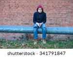 Young Homeless Boy Sits On A...