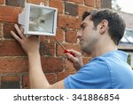 man fitting security light to... | Shutterstock . vector #341886854
