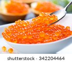 Small photo of Caviar. Red caviar in spoon on a white background. Gourmet food close up