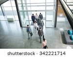 Small photo of Group of professional business people walking on the way in building