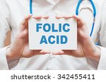 Small photo of Folic Acid written on a card in doctors hands
