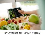 woman following recipe on... | Shutterstock . vector #343474889