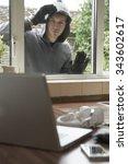 Burglar Looking At Valuables Through House Window - stock photo