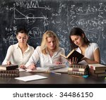 schoolmate studying and reading books against a blackboard - stock photo