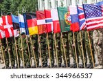 RUKLA, LITHUANIA - JUNE 8, 2015: NATO soldiers holding alliance flags - stock photo