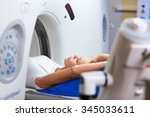 Stock photo pretty young woman goiing through a computerized axial tomography cat scan medical test 345033611