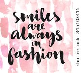 Smiles are always in fashion. Inspirational quote handwritten with black ink and brush, custom lettering for posters, t-shirts and cards. Vector calligraphy on pink watercolor strokes background. | Shutterstock vector #345103415