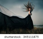 Fashion female model with long blowing hair outdoor. Portrait of sexy glamour woman with healthy and beauty flying fluttering long brown hair  wearing  black dress resists strong wind. Copy space.