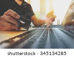 hands using laptop and holding... | Shutterstock . vector #345134285