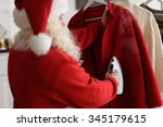 santa claus at home ironing his ... | Shutterstock . vector #345179615