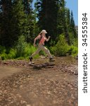 Female Hiker Leaping Across A...