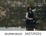 Small photo of caucasian gold digger in retro clothes washes gold in metal bowl in lake with rocky bank. He wears hat, shirt, leather pants, vest, boots. He sits on the rock in the water. Sky is cloudy and grey.