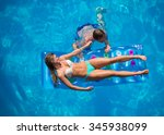 young couple relaxing on a lilo ... | Shutterstock . vector #345938099