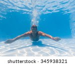 Young Man Swimming Underwater...