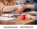 Small photo of Sealing a deal. Close-up of two men shaking hands while sitting at the wooden desk