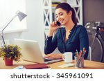 Sharing good business news. Attractive young woman talking on the mobile phone and smiling while sitting at her working place in office and looking at laptop