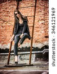 Small photo of Fashion female model alluring outdoor by the brick wall. City style. Fashion photo.