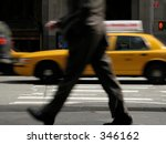 This is a motion blur of a business man walking down the street with a moving cab in the background. - stock photo