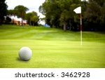 golf ball near the putting green in a very sunny day - stock photo