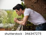 Small photo of Handsome dark haired young man wearing a v-neck white T-shirt while smoking a cigarette in a balcony standing