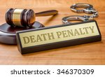 Small photo of A gavel and a name plate with the engraving Death Penalty