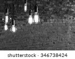 Stock photo decorative antique edison style light bulbs against brick wall background 346738424