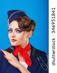 Small photo of Stewardess posing with face art. Young attractive girl in a blue suit flight attendants. Airfreight. Service.