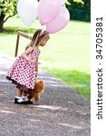 Little girl at a park with pink and white balloons and a little brown teddy. - stock photo