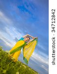 Indian Woman in traditional Sari  / blue sky and green grass - stock photo
