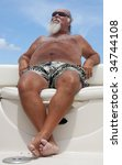 Older man relaxes on a summer day sitting on a boat with a blue sky in the background. - stock photo