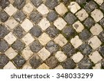 Small photo of A cobblestone sidewalk in the Alfama neighborhood of Lisbon has arranged the light and dark stones in an alternating pattern like a checker board.